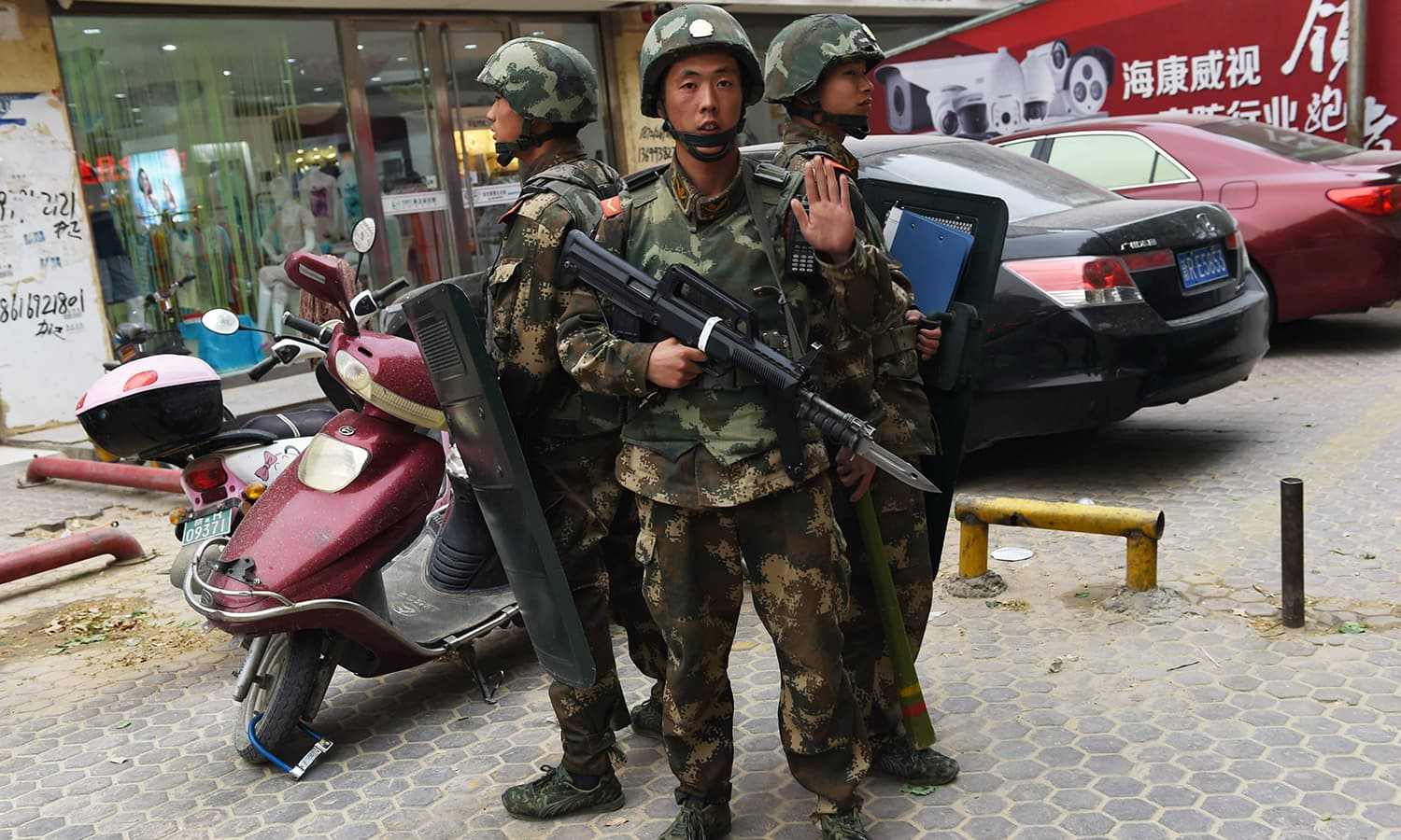 Paramilitary police officers stand guard outside a shopping mall in Hotan in China's western Xinjiang region in this April 16, 2015 photo. — AFP
