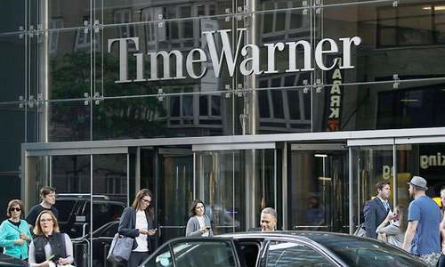 In this file photo taken on June 12, 2018, people walk past the Time Warner Centre in New York City. —AFP