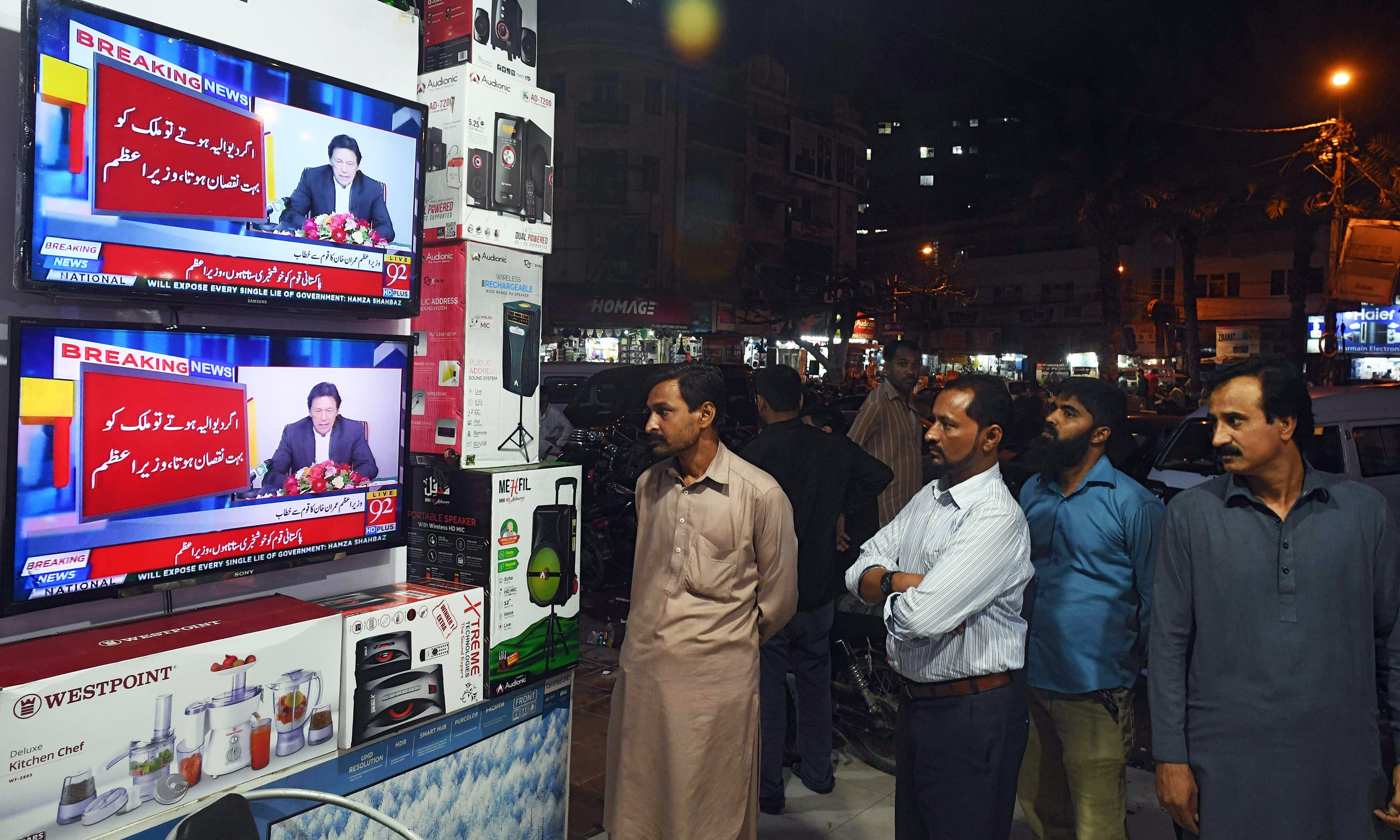 People watch the speech of Prime Minister Imran Khan as he addresses the nation, at an electronic shop in Karachi on Wednesday. — AFP