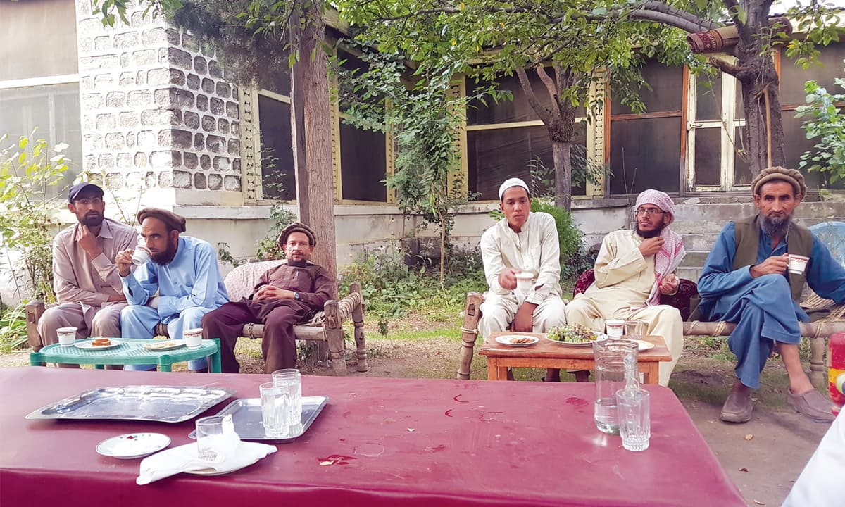A school burning suspect, Sirajul Haq (third from right), awaits the police to take him into custody