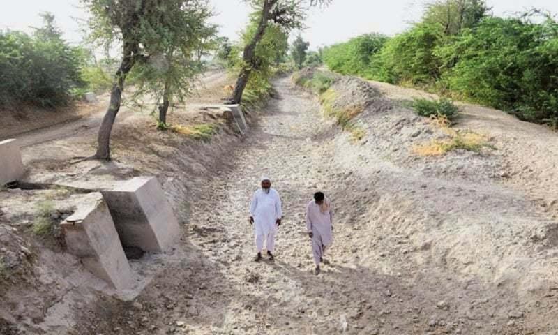 دیہاتی بدین کے ایک خشک کینال میں چل رہے ہیں۔ دریائے سندھ سے پانی نہ آنے کی وجہ سے اس سال فصلوں کی بوائی شدید متاثر ہوئی ہے۔ — ڈان فائل فوٹو۔