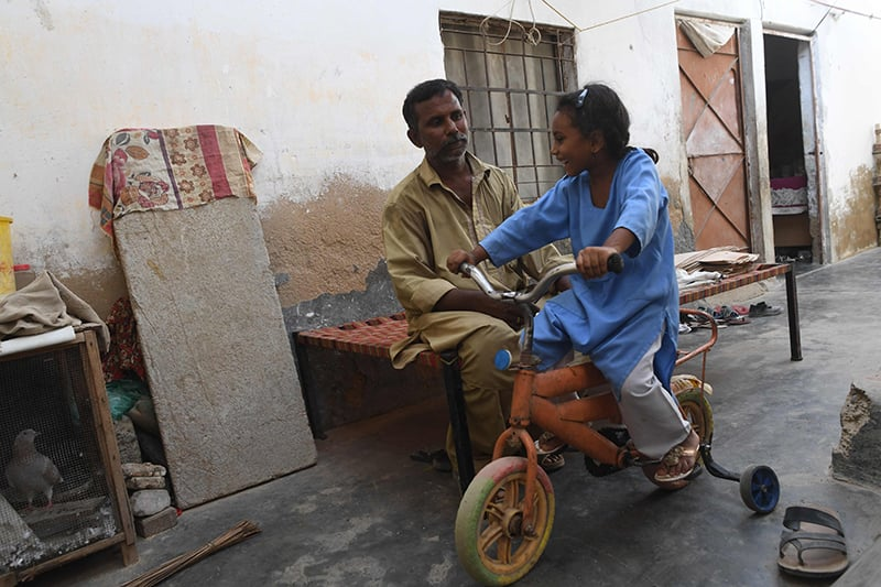 Auto-rickshaw driver Mohammad Rasheed plays with his daughter Nabeeha Rasheed in their home in Korangi. ─ AFP
