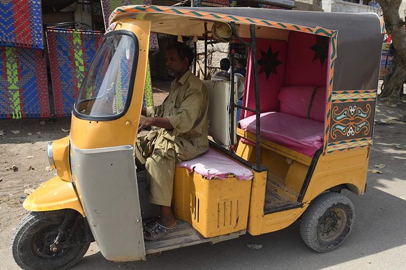 Auto-rickshaw driver Mohammad Rasheed drives his rickshaw in Korangi. ─ AFP