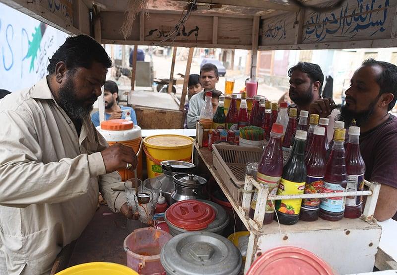 Falooda vendor Mohammad Qadir (L) prepares falooda for customers at his cart in Orangi Town. ─ AFP