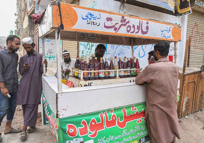 Falooda vendor Mohammad Qadir prepares falooda for customers at his cart in Orangi Town. ─ AFP
