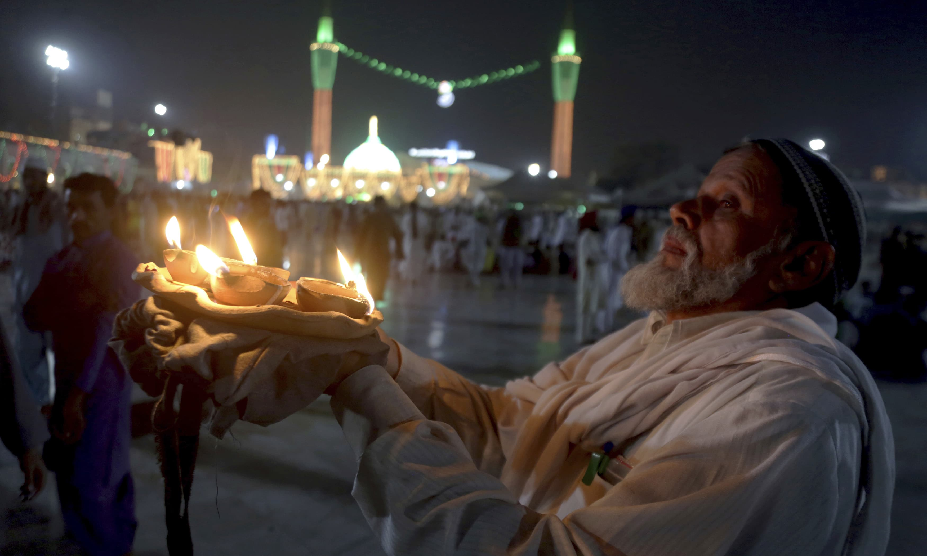 A devotee arrives with clay-lamps during the celebrations of the three-day annual festival of famous saint Hazrat Data Ganjbaksh at his shrine in Lahore. —AP