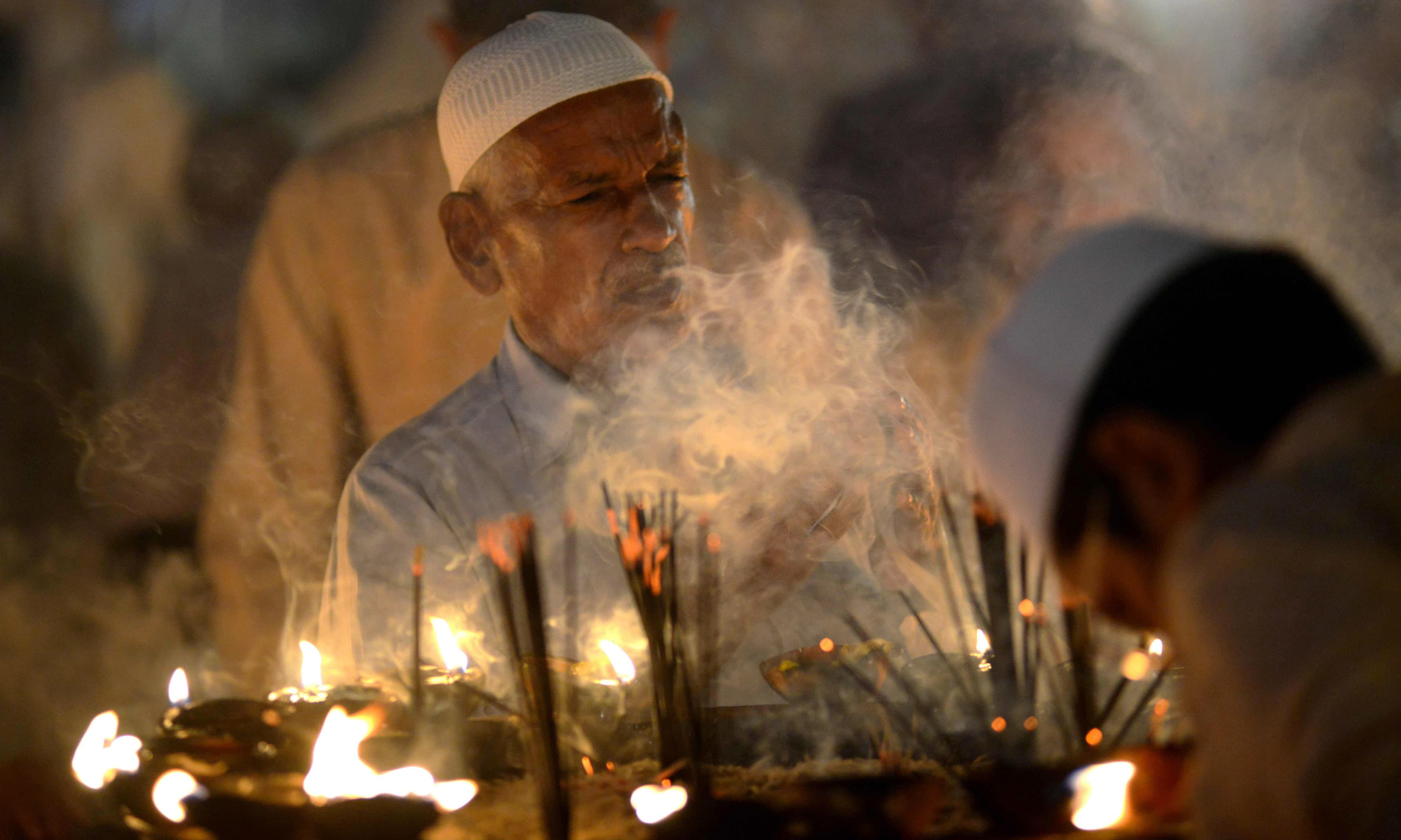 Sufi disciples light lamps at the Data Darbar complex during the three-day annual 'Urs' in Lahore. —AFP