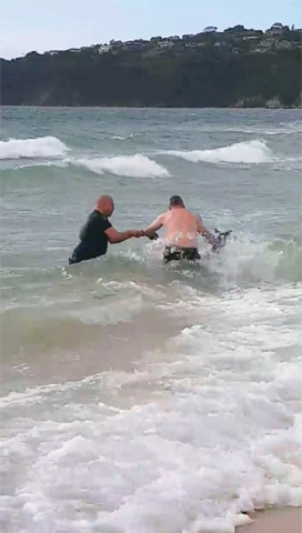 Police officers try to rescue a kangaroo struggling in the sea at Safety Beach in this still image taken from a video.—Reuters