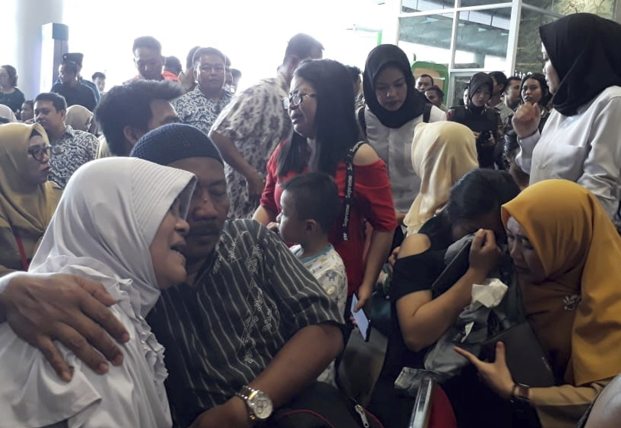 Relatives of passengers comfort each other as they wait for news on a Lion Air plane that crashed off Java Island at Depati Amir Airport in Pangkal Pinang on Monday. ─ AP