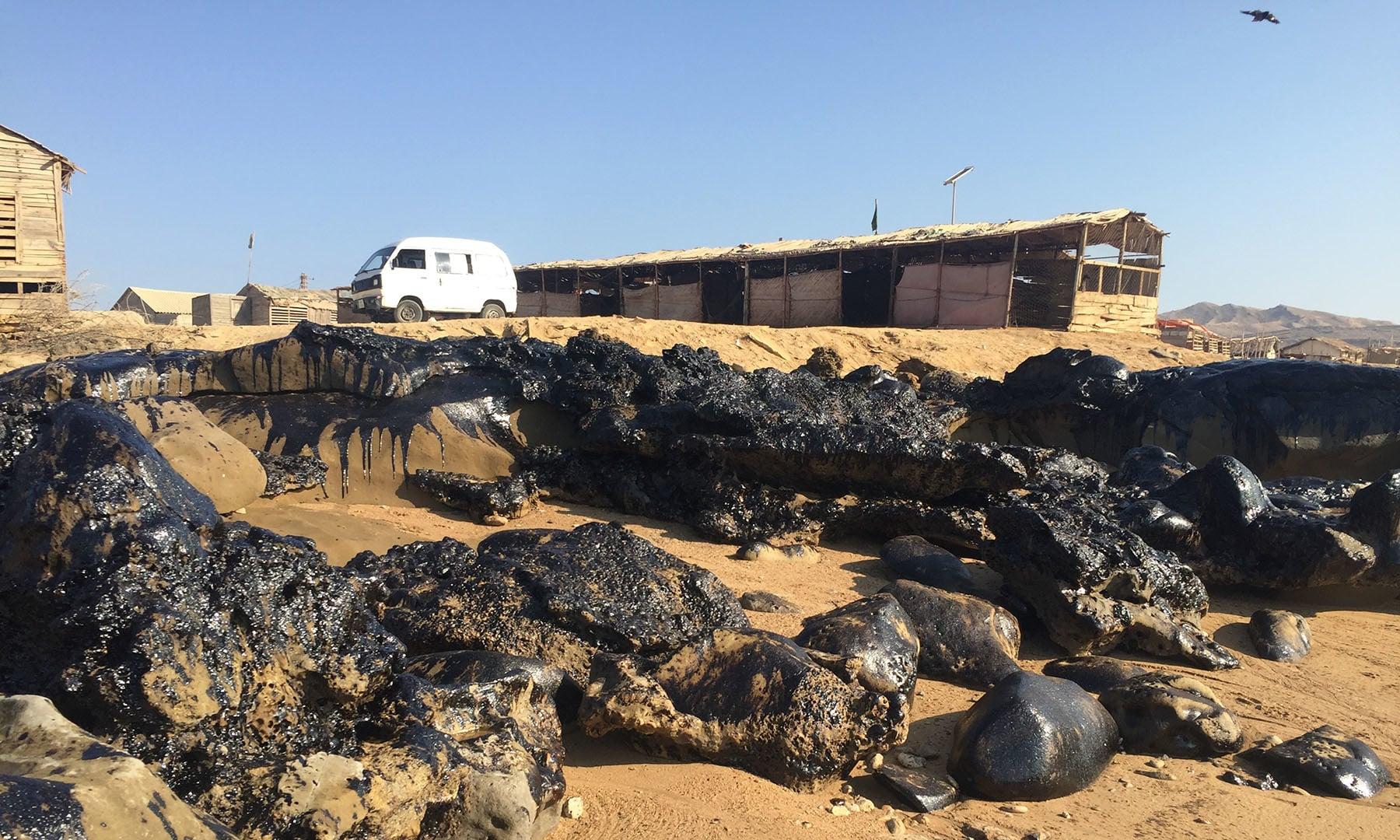 مبارک گوٹھ میں سمندر کے کنارے پر تیل بکھرا ہوا پڑا ہے۔— فوٹو سعید الاسلام