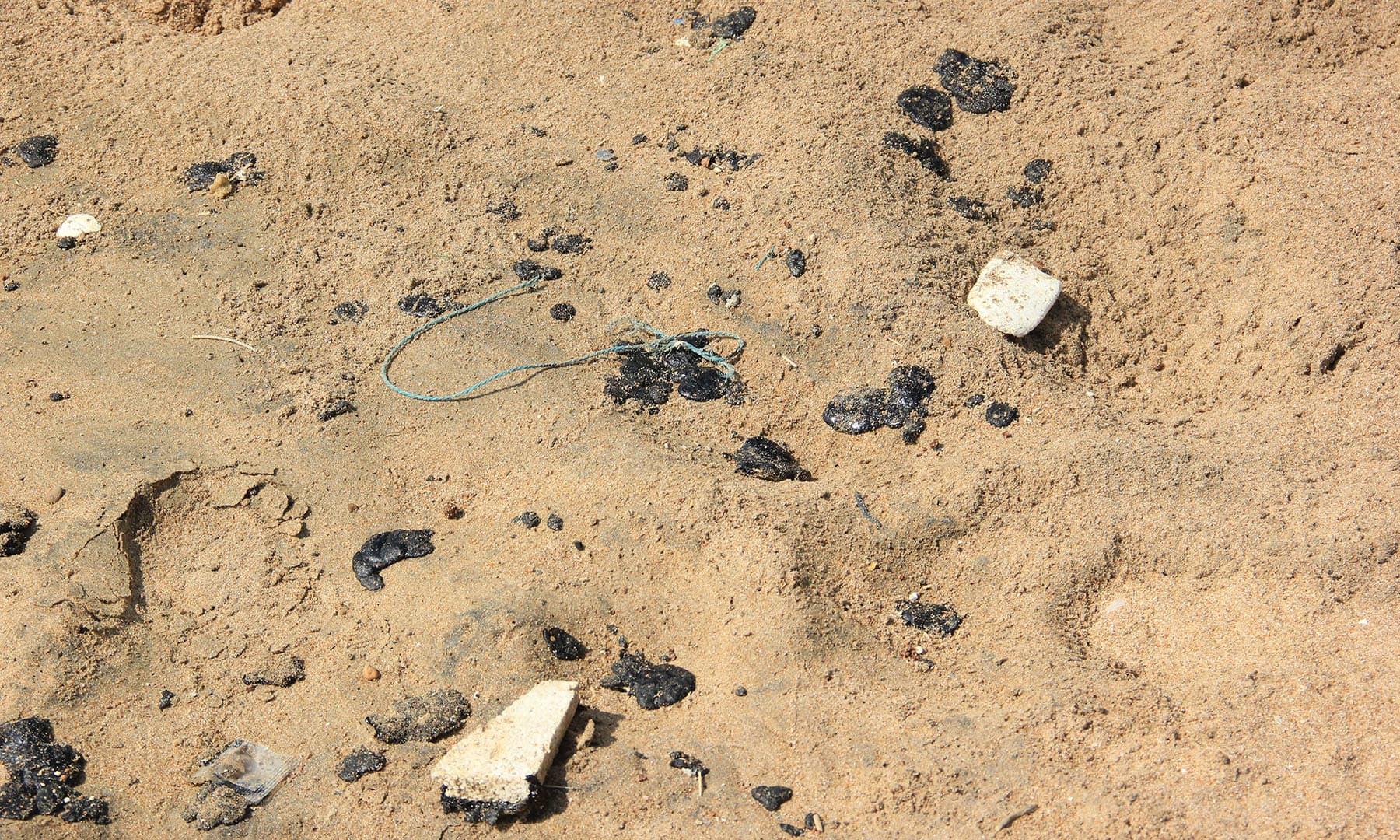 سمندر کے کنارے ریت پر تیل بکھرا پڑا ہے— فوٹو سعید الاسلام