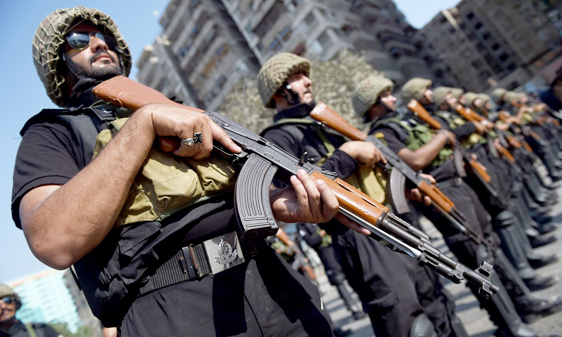 Pakistani police commandos stand guard along a street. —AFP