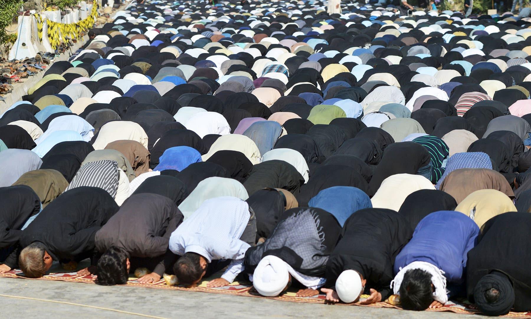 Devotees offering noon prayers in Karachi. —AFP