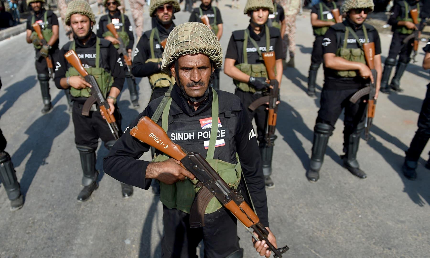 Police commandos patrol along a Karachi street. —AFP