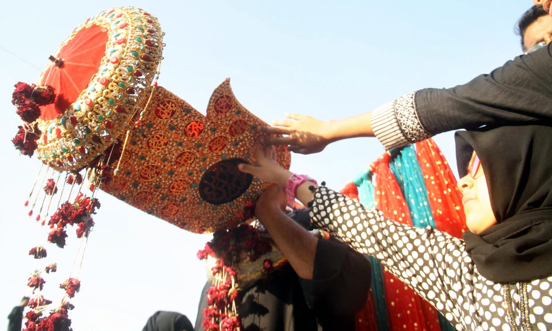 A young girl touching the *alam* in the procession taken out in Karachi. —APP