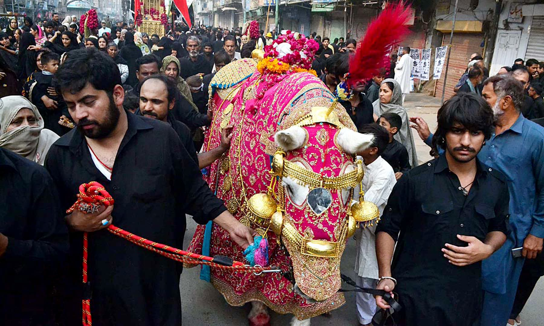 Mourners participating in the procession at Goole Chowk in Sargodha. —APP