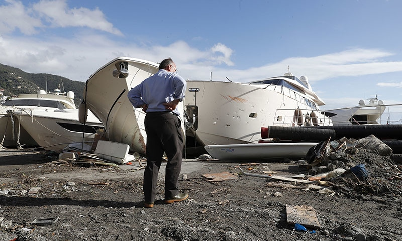 A man looks at the damage of boats washed ashore, a day after a storm, in Rapallo, northern Italy, on Tuesday. — AP
