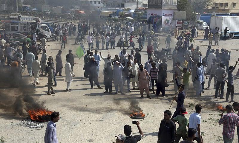Protesters in Karachi burn tires. — AP