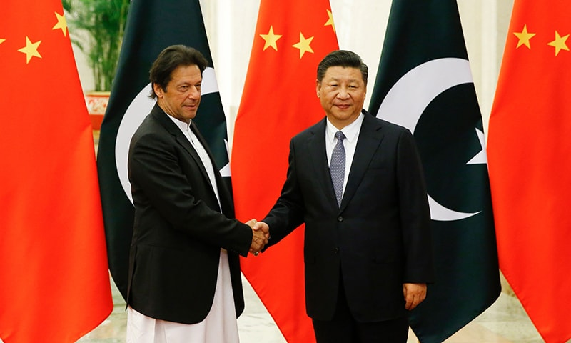 Prime Minister Imran Khan (L) shakes hands with Chinese President Xi Jinping (R). ─ AFP