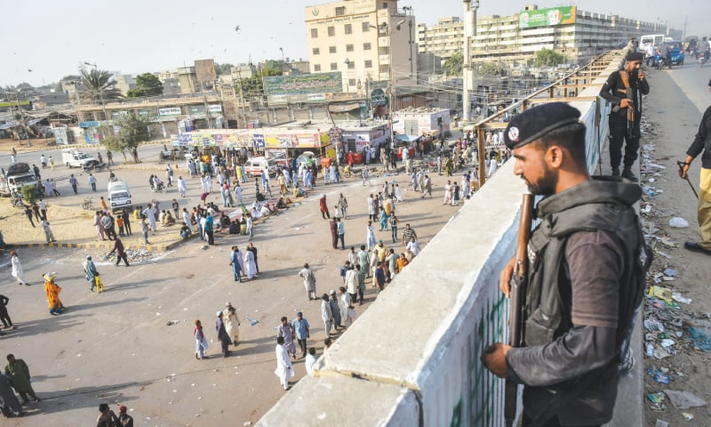 POLICE personnel watch protesters from a safe distance in Liaquatabad on Friday.—Fahim Siddiqi / White Star