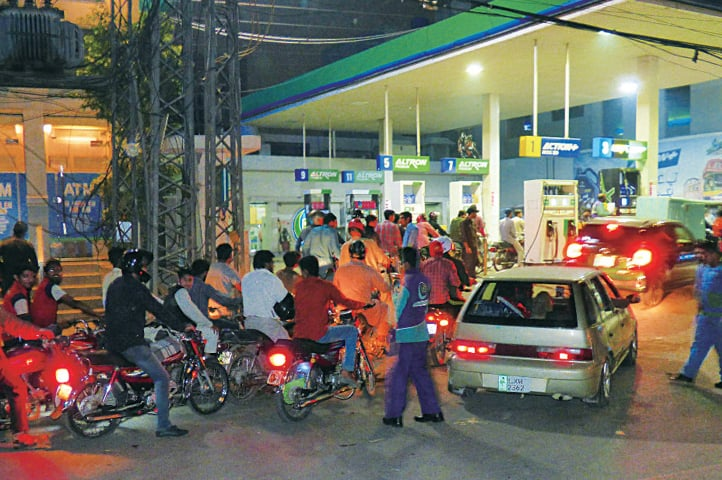 Motorists throng a filling station following the shortage of petrol in the city. — White Star