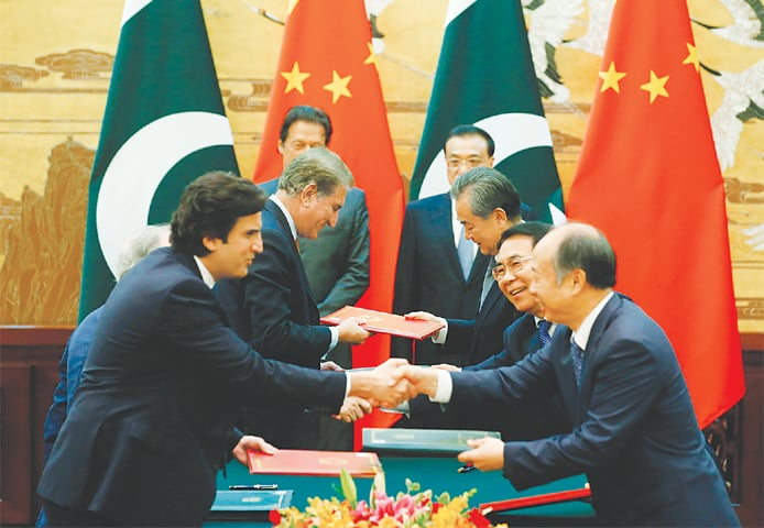 BEIJING: Pakistani and Chinese officials shake hands and exchange documents during a ceremony also attended by Prime Minister Imran Khan and Premier Li Keqiang at the Great Hall of the People on Saturday.—AFP