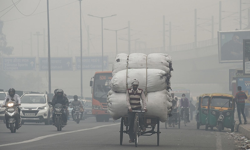 Vehicles drive past amids heavy smog along a busy road in New Delhi on November 5. — AFP