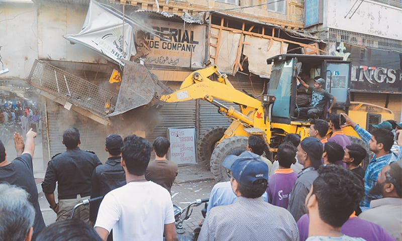 HEAVY machinery is being used to remove an illegal signboard in Saddar on Friday. However, as seen on the right, encroachers carry on business as usual under the nose of civic authorities.—White Star
