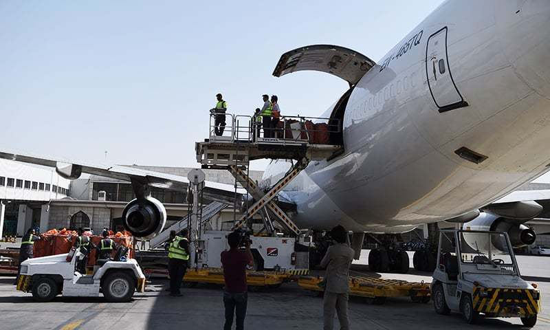 Afghan airport workers load a cargo plane. ─ AFP
