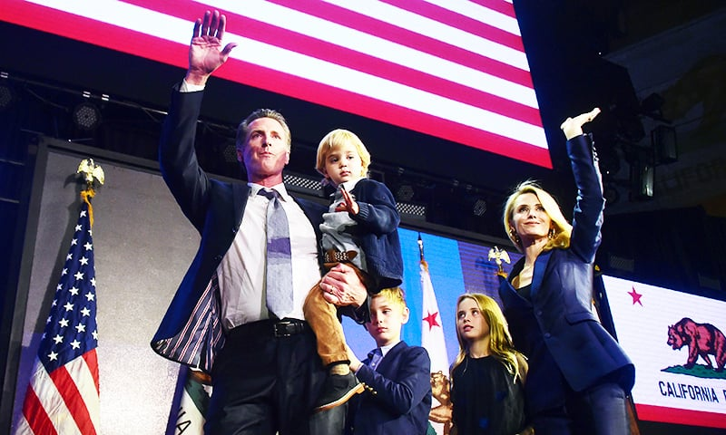 California's Democratic gubernatorial candidate Gavin Newsom and his family waves to supporters from stage at his election night watch party in Los Angeles, California on November 6, 2018.  Gavin Newsom defeated his Republican opponent John Cox.—AFP