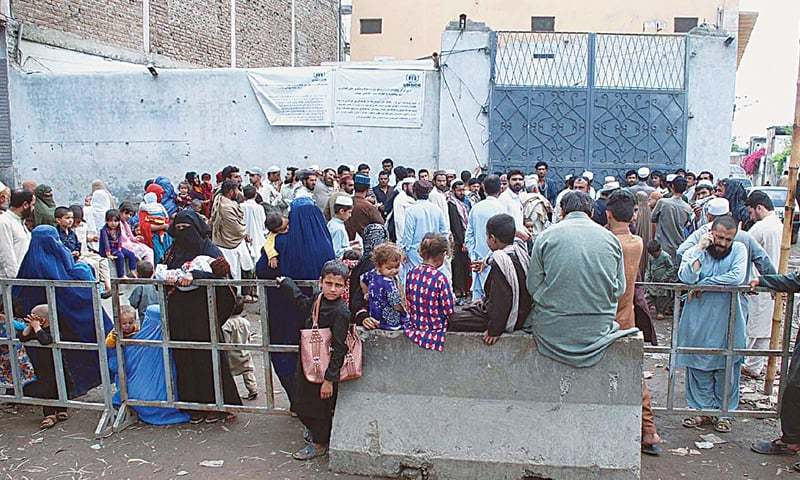 This April 2017 file photo shows Afghan refugees gathered outside a registration point of the UNHCR in the Chamkani area for repatriation. — APP/File