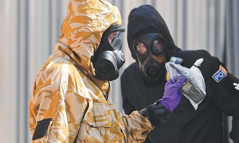 In this file photo, an  investigator wearing a camouflaged protective suit, gloves and a gas mask works with a policeman in protective suit outside the John Baker House Sanctuary Supported Living in Amesbury, southern England. —AFP/File photo