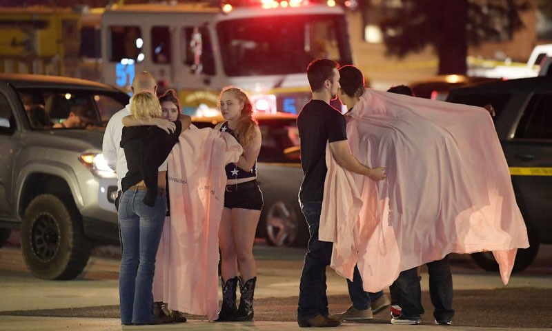 People comfort each other as they stand near the scene of a shooting at the Borderline Bar & Grill in Thousand Oaks, California — AP