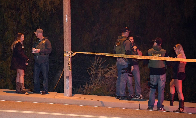 پولیس کی ٹیم شراب خانے میں پیش آنے والے واقعے کے بعد عینی شاہدین کے بیانات لے رہی ہے— فوٹو: اے ایف پی