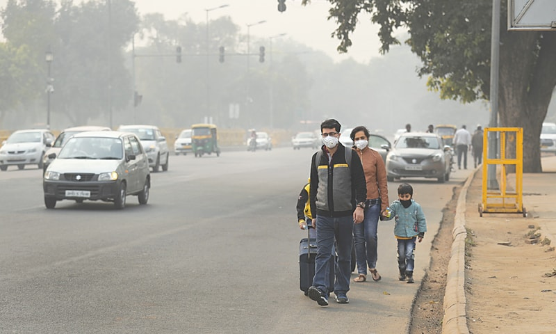 New Delhi: Members of a family wearing pollution masks look for transport a day after Diwali.—AP