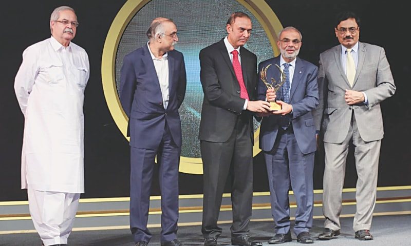 PRESIDENT and CEO of Meezan Bank Irfan Siddiqui receives the best bank of the year award from Deputy Governor of the State Bank of Pakistan Jameel Ahmed at the 3rd Pakistan Banking Awards ceremony on Friday. S.M. Shabbar Zaidi (Territory Senior Partner — A.F. Ferguson & co.) and Farooq Sheikh (acting CEO, IBP) are also seen.—Dawn
