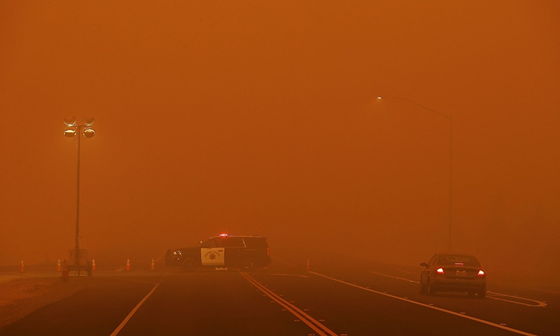 A California Highway Patrol vehicle mans a checkpoint along Highway 32 as the Camp Fire burns in the area. — AFP