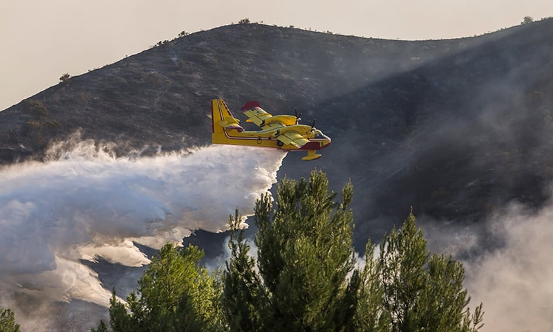 An airplane drops water on wildfires close to the 101 Freeway in Thousands Oaks, California. — AFP