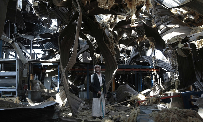 In this September 2016 file photo, a man stands among the rubble of the Alsonidar Group's water pump and pipe factory after it was hit by Saudi-led airstrikes in Sanaa, Yemen.  — AP