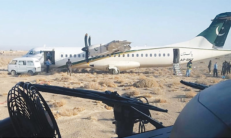 PANJGUR: Security personnel inspect the PIA plane after it skidded off the runway at Panjgur Airport on Saturday.—Online