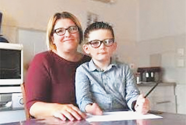 LOUIS, soon to be 8 years old, with his mother. He was born with a deformed right hand.
