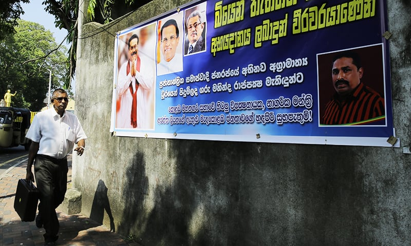 A Sri Lankan man walks past a banner carrying portraits of newly appointed prime minister Mahinda Rajapaksa, left, his brother Gotabhaya and president Maithripla Sirisena, second left, outside the supreme courts complex.—AP