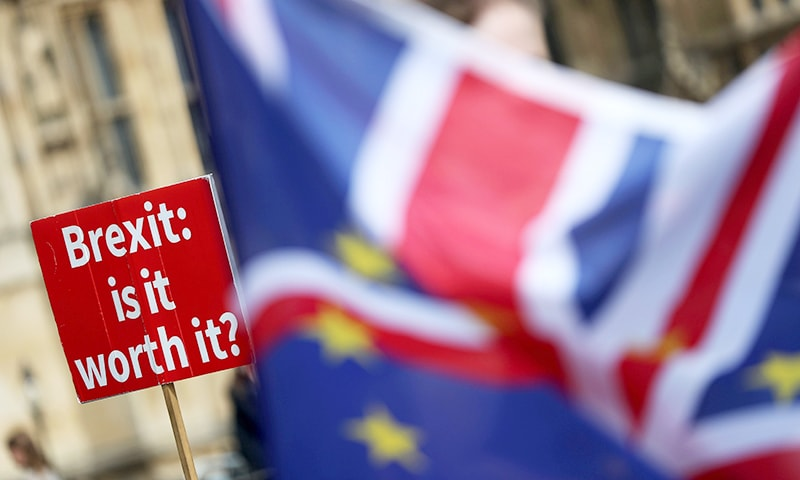 "In this file photo taken on September 10, 2018, a demonstrator holds a sign that reads ""Brexit. Is it worth it?"" whilst draped in European Union (EU) and Union flags, as he protests outside the Houses of Parliament in central London. —AFP"
