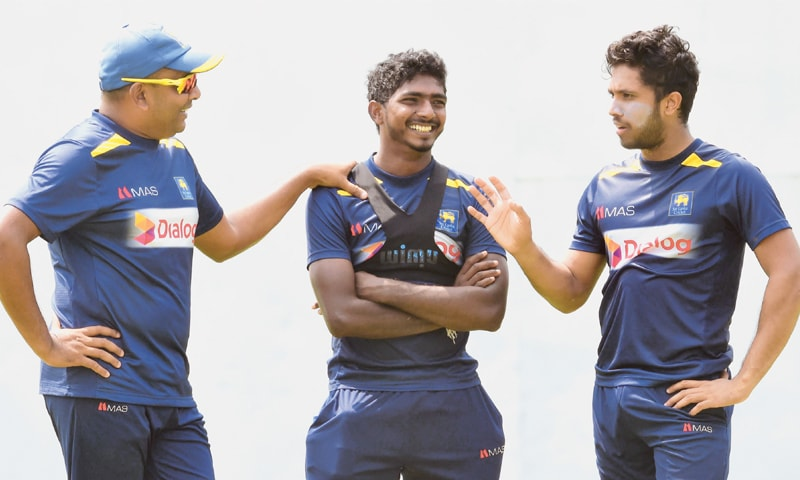 PALLEKELE: Sri Lankan cricketers Lakshan Sandakan (C) and Kusal Mendis (R) share a light moment with spin bowling coach Piyal Wijetunge during a practice session at the Pallekele International Cricket Stadium on Tuesday.— AFP