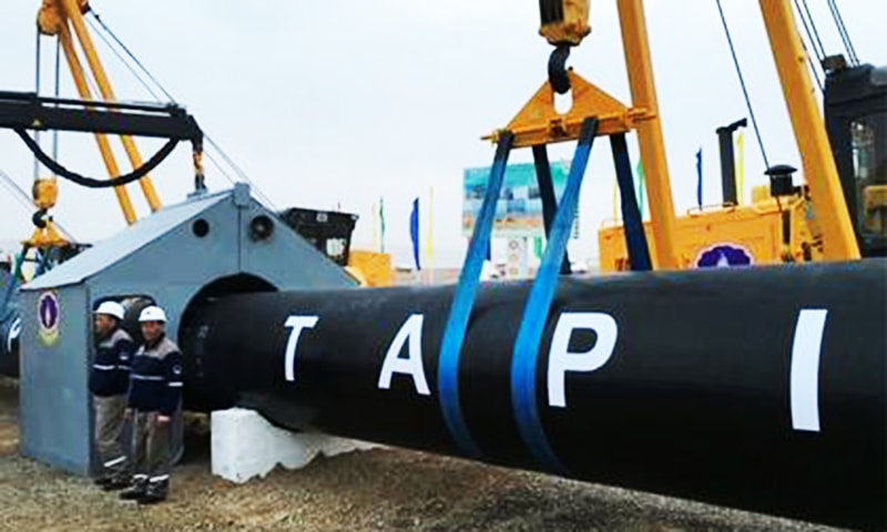 Workers stand near a gas pipe during the launching ceremony of construction work on the Afghan section of TAPI.— File photo