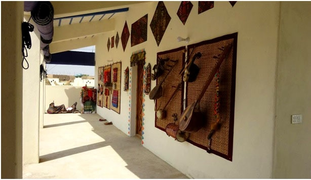 The front wall of the model house showcasing traditional Sindhi instrument, Tamboora, and several pieces of embroidery.—Photo by  Vikram Das and Nirmal Riaz