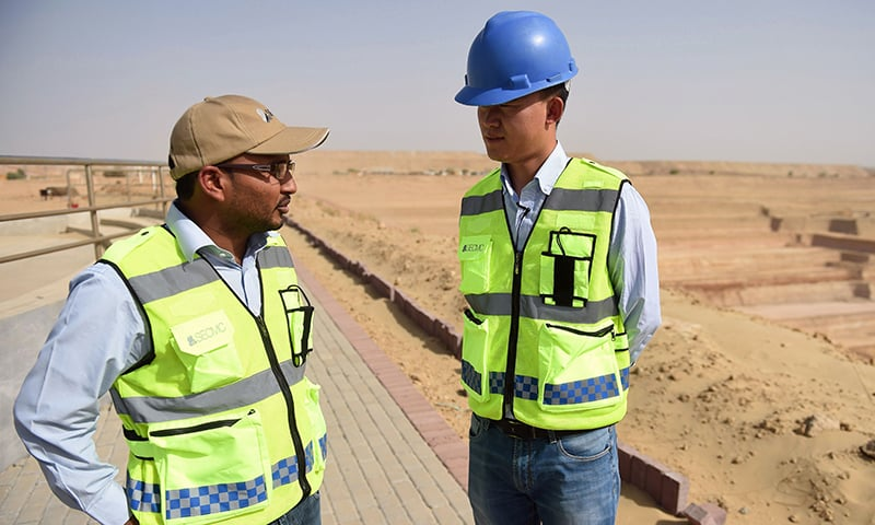 Chinese Technical Director Yan Bing Bing (R) talking with a co-worker at an open-pit coal mining site at Islamkot in Tharparkar. ─AFP