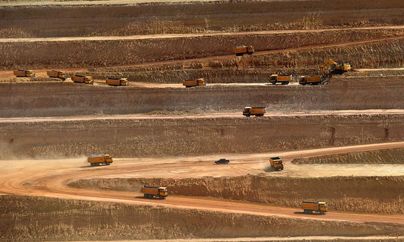 Trucks transporting soil in an open-pit coal mining site at Islamkot. ─AFP