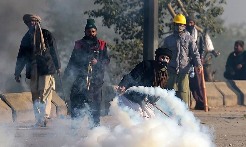 In this file photo, a protester throws a tear gas shell back towards police during a clash at the Faizabad sit-in site. ─ AFP