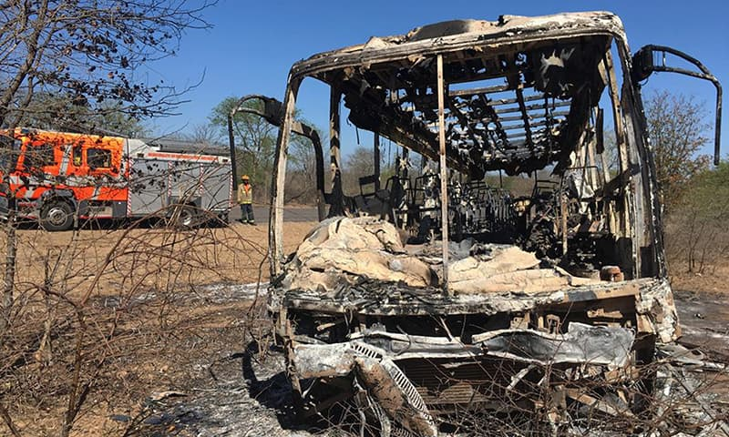 A fire engine is parked near to a burnt out bus after a bus accident in Gwanda about 550 kilometres south of the capital Harare. — AP